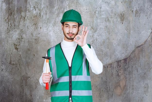 Ingenieursmann in gelber uniform und helm, der eine holzaxt zur reparatur hält und freudenhandzeichen zeigt