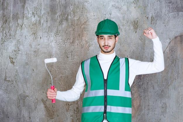 Ingenieursmann in gelber uniform und helm, der eine trimmrolle für die wandmalerei hält und ein positives handzeichen zeigt.