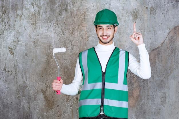 Ingenieursmann in gelber uniform und helm, der eine trimmrolle für die wandmalerei hält und nachdenklich aussieht