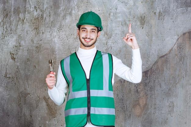 Ingenieursmann in gelber uniform und helm, der einen metallschlüssel zur reparatur hält und nachdenklich aussieht