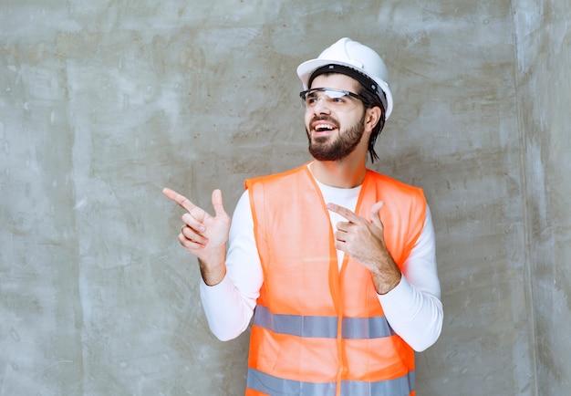 Ingenieursmann mit weißem helm und schutzbrille, der auf seinen kollegen oder auf etwas beiseite zeigt.