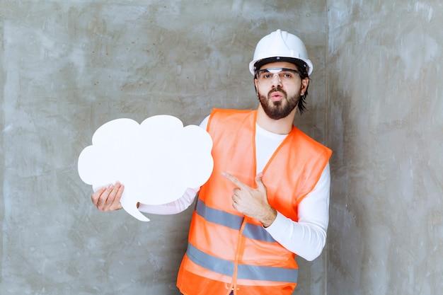 Ingenieursmann mit weißem helm und schutzbrille, der eine infotafel hält.
