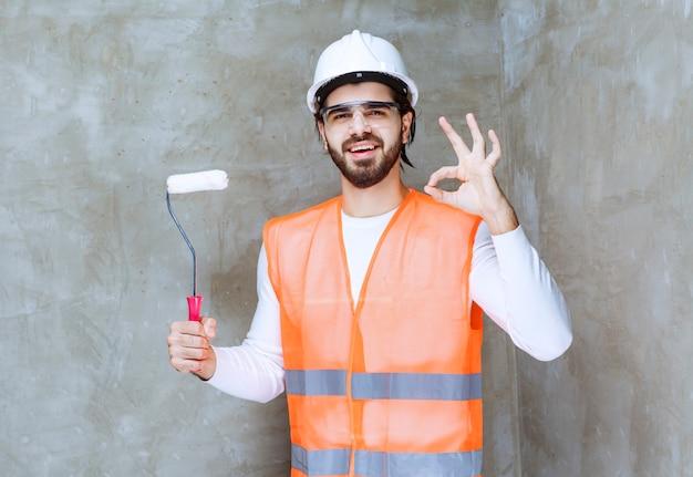 Ingenieursmann mit weißem helm und schutzbrille, der eine weiße trimmrolle hält und ein genusszeichen zeigt.