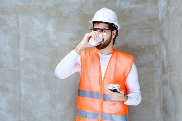 Ingenieursmann mit weißem helm und schutzbrille, der einen wecker hält und eine tasse tee trinkt.