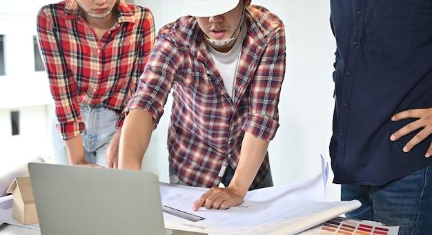 Ingenieurteam diskutieren und arbeiten auf der baustelle. eigentümerinspektion bei dorfprojekt und gutsgebäude.