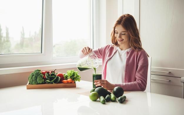 Ingwer dame mit sommersprossen, die etwas grünen gemüsesaft in das glas geben und in der nähe einiger früchte lächeln