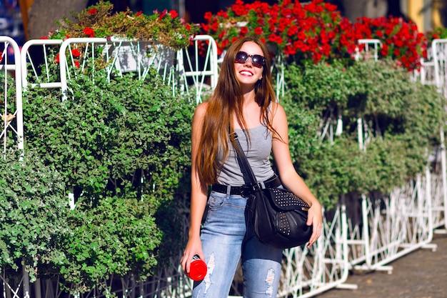 Ingwer-hipster-mädchen verbringen erstaunlichen sonnigen tag im freien, reisen in europa, lässiger hipster-look, trinken leckeres latte-kaffeegetränk zum mitnehmen, genießen urlaub und entspannen.