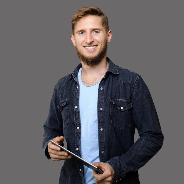 Ingwer kaukasischer mann mit bart, der eine tablette hält und it-dienste beim lächeln auf einer grauen wand fördert