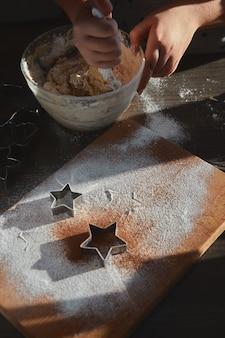 Ingwer-keksteig machen. die hände einer jungen frau mischen sich in einer glasplatte, um den lebkuchenmannenteig zu backen. das konzept eines festmahls im haus, eines familienessens.