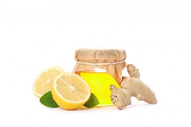 Ingwer, zitronen und glas mit honig lokalisiert auf weiß