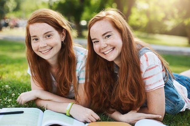 Ingwer-zwillingsmädchen verbringen ihre sommerferien, um sich auf die universitätsprüfungen vorzubereiten. zukünftiger arzt und anwalt, die spaß haben, an einem sonnigen tag im park lächelnd zu haben.