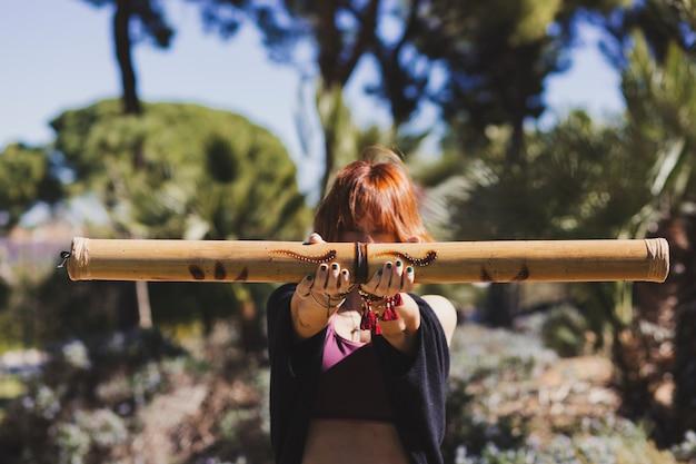 Ingwerfrau, die bambusstock zeigt