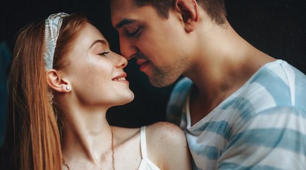 Ingwerfrau mit sommersprossen und ihrem brünetten liebhaber, die sich küssen und zeit miteinander verbringen