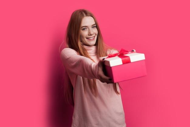 Ingwerfrau mit sommersprossen und roten haaren lächelt und gibt an der kamera eine rote schachtel mit geschenk, das auf einer roten wand aufwirft