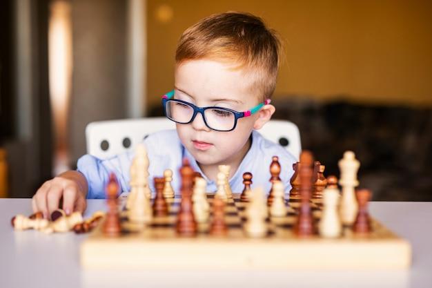 Ingwerjunge mit down-syndrom mit den großen gläsern, die zu hause schach spielen