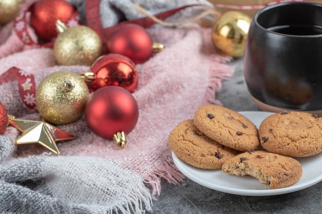 Ingwerkekse in einer weißen untertasse mit weihnachtsfiguren herum