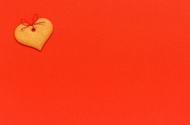 Ingwerplätzchen herzförmig verziert mit einem bogen auf einem rot