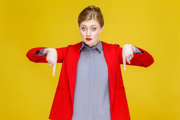 Ingwerrote kopffrau im roten anzug wünscht sich, nach unten auf den kopierraum zu zeigen