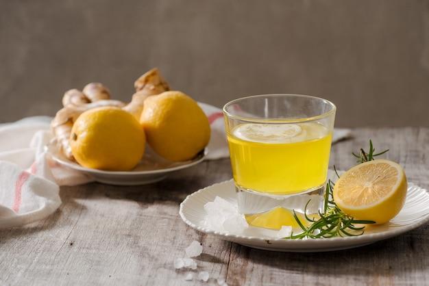 Ingwertee mit zitrone, ingwerwurzel und rosmarin auf holztisch. kleiner transparenter glaskrug mit heißem getränk.