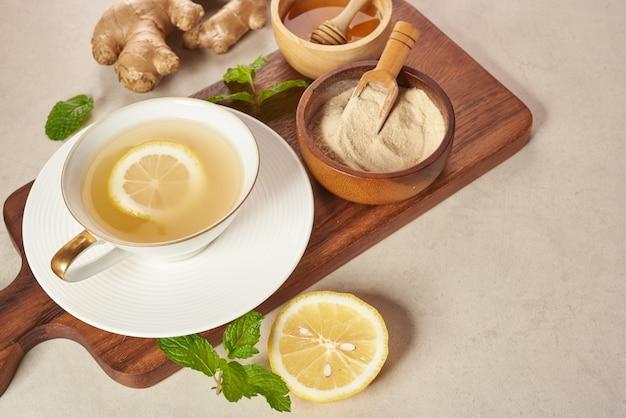 Ingwertee zutaten, gesunde tröstende und erhitzende tee nach einfachem rezept. ingwertee und zutaten - zitrone, honig. draufsicht. flach liegen. frisch aus heimischem wachstum bio-garten. lebensmittelkonzept.