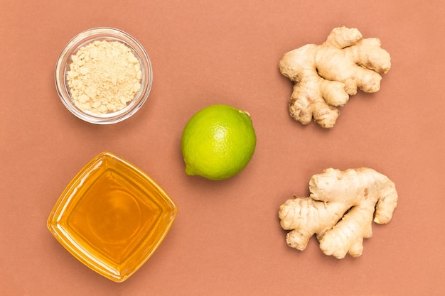 Ingwerwurzel und honig in glasschalen mit rohen ingwerwurzeln und limette