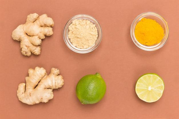 Ingwerwurzel und honig in glasschüssel, grüne limette, trockener ingwer und kurkuma in glasschüssel