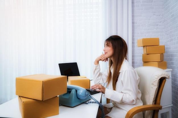 Inhaber des kleinbetriebs der frauen, der zu hause mit verpackungskasten auf arbeitsplatz arbeitet