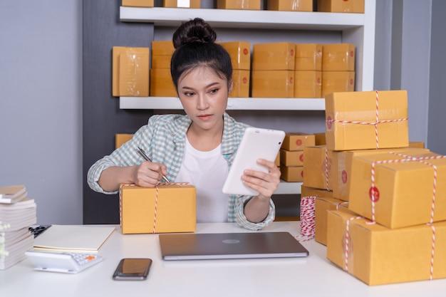 Inhaber des kleinen online-geschäfts, die frau, die mit digitaler tablette arbeitet, bereiten paketkästen für liefern vor