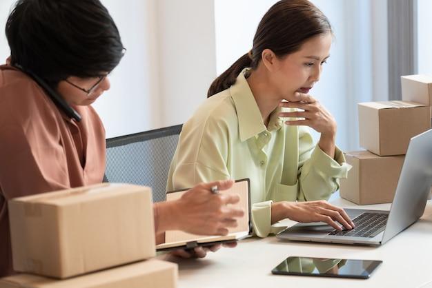 Inhaber eines asiatischen geschäftspaares, das zu hause mit der verpackungsschachtel ihres online-geschäfts arbeitet, bereiten vor, produkte an kunden zu liefern