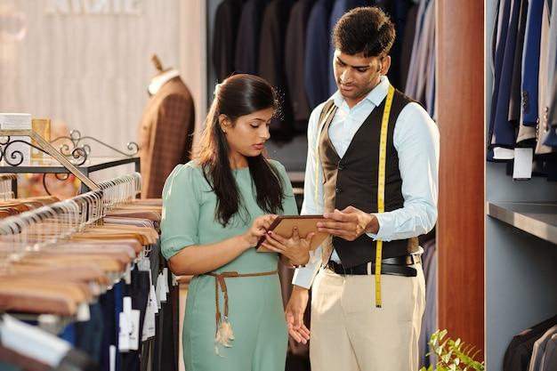 Inhaber eines herrenbekleidungsgeschäfts bespricht katalog auf tablet-computer mit assistent