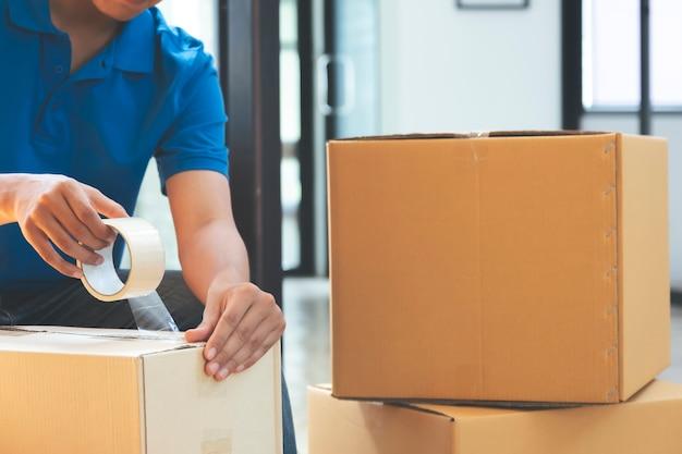 Inhaber eines kleinen online-geschäfts, der in den karton packt.