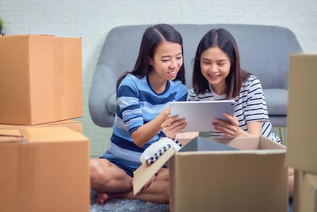 Inhaber mit zwei asiaten überprüfen den kundenauftrag von der tablette, verkäufer bereitet den lieferungskasten vor. startup small business-konzept.