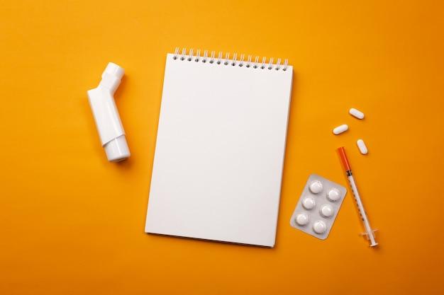 Inhalator in doktorschreibtisch mit notizbuch und pillen, draufsicht