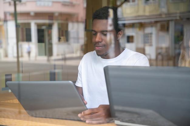 Inhalt afroamerikaner kerl, der am tisch sitzt und laptop verwendet