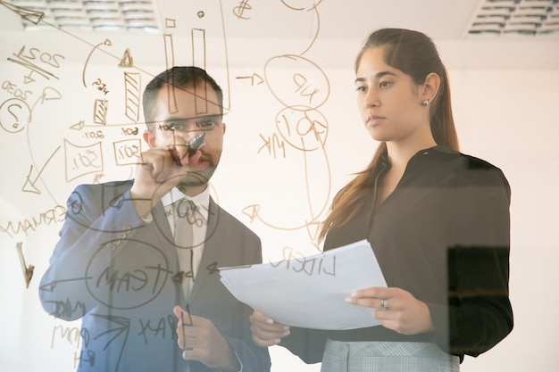 Inhalt afroamerikaner manager, der diagramm auf glasplatte schreibt. professionelle junge hübsche kollegin, die dokument hält und grafik im konferenzraum betrachtet. teamwork und marketingkonzept
