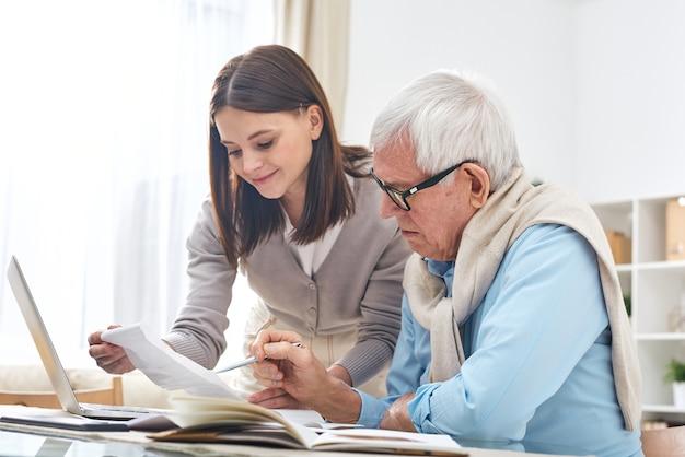 Inhalt attraktive junge tochter, die älteren vater hilft, rechnungen zu bezahlen und finanzen zu überprüfen