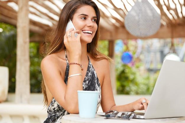 Inhalt brünette frau mit fröhlichem ausdruck, hat freundliche unterhaltung mit der besten freundin, surft im internet auf einem tragbaren laptop, genießt frische heiße getränke im café, hat pause nach der arbeit