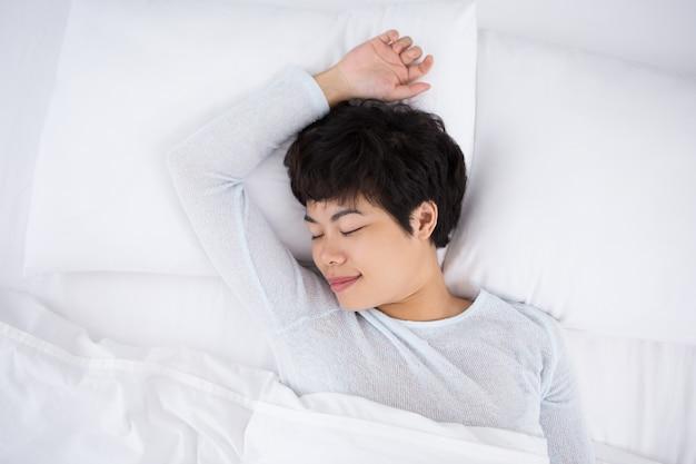 Inhalt hübsches asiatisches mädchen schläft im bett