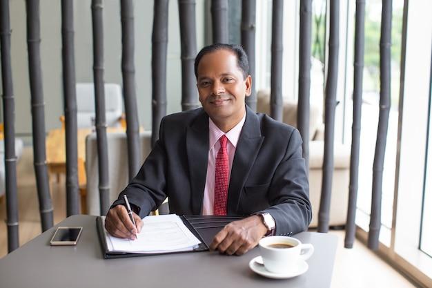Inhalt indischer geschäftsmann, der form im cafe vervollständigt