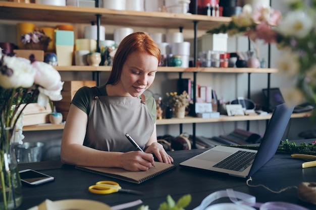 Inhalt qualifizierte junge floristin mit roten haaren, die am schreibtisch stehen und notizen im skizzenblock machen, während sie im blumenladen arbeiten