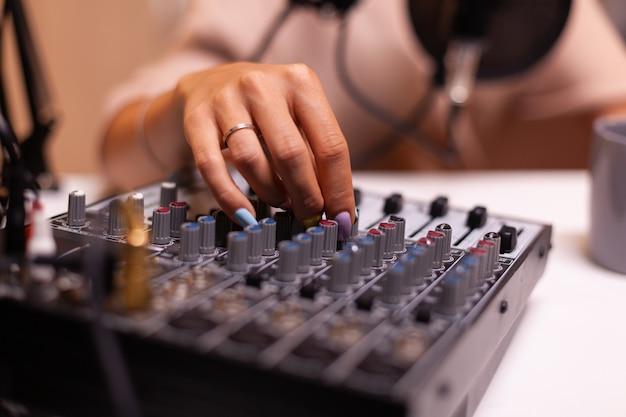 Inhaltsersteller überprüft den ton auf dem dj-mixer für einen besseren podcast