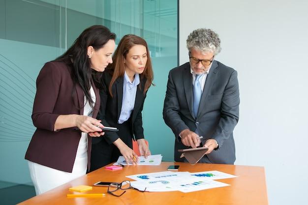 Inhaltsgeschäftsleute, die daten auf tablettbildschirm beobachten