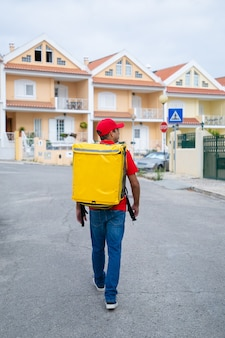 Inhaltslieferant, der gelben wärmebeutel trägt. kurier mittleren alters im roten hemd auf der suche nach adresse und lieferauftrag.
