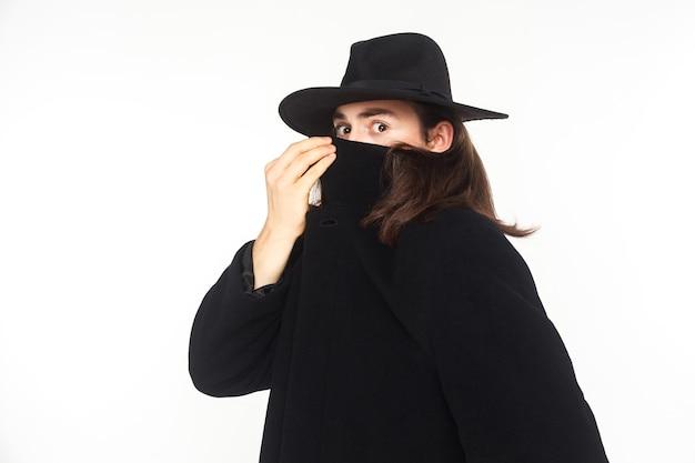 Inkognito geheimagent spion, der mit großen augen in die kamera schaut. studioaufnahme