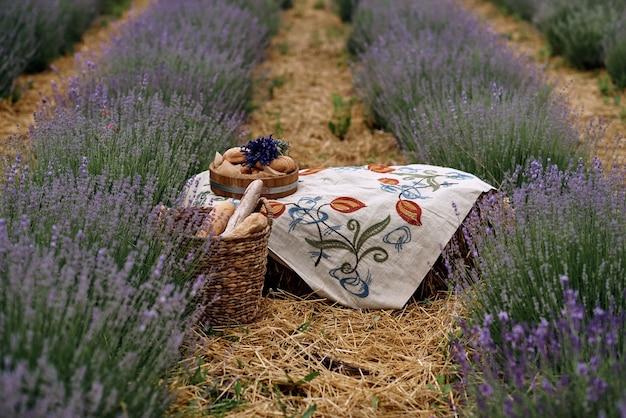 Inmitten eines lavendelfeldes liegt eine bestickte tischdecke.