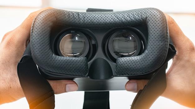 Innen eines vr- oder ar-kopfhörers auf weiß schauen. hand, die vr-gläser hält.