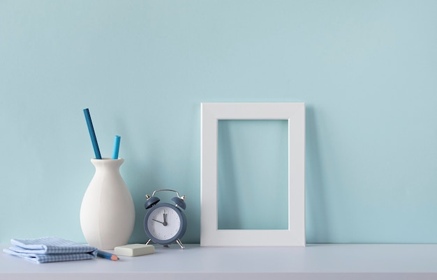 Innen mit blauton. arbeitsplatz des designers. weißer hölzerner leerer rahmen auf einem schreibtisch, wecker, vase mit bleistiften. modell mit platz für text.