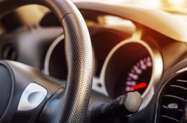 Innenansicht des autos mit dem schwarzen modernen lederlenkrad-armaturenbrett. selektiver fokus. geringe schärfentiefe. nahansicht.