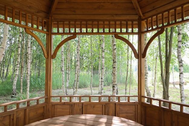 Innenansicht des offenen sommerpavillons aus holz im birkenhain
