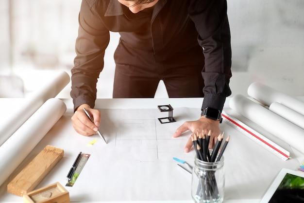 Innenarchitekt, der an den plänen am kreativen studioarbeitsplatz arbeitet.